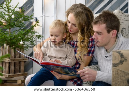 nice parents and a small child reading a book at Christmas