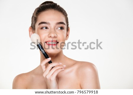 Nice photo of attractive half-naked woman with fresh skin holding brush for makeup close to face, and looking aside isolated over white wall copy space