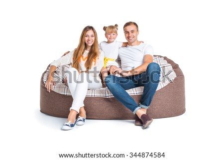 Nice photo of young family of three isolated on white background. Young man, woman and their little daughter smiling and sitting on big cushioned frameless couch - stock photo