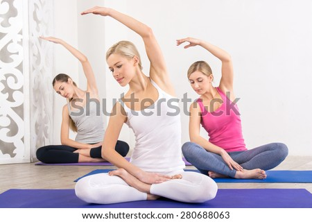 Nice photo of young three women practicing yoga. Women doing lotus pose on fitness mats. White interior