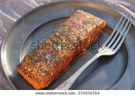 Nice piece of smoked salmon seasoned with salt and chopped dill.