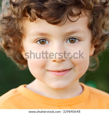 Nice portrait of a little boy with curly hair and brown eyes smiling - stock photo