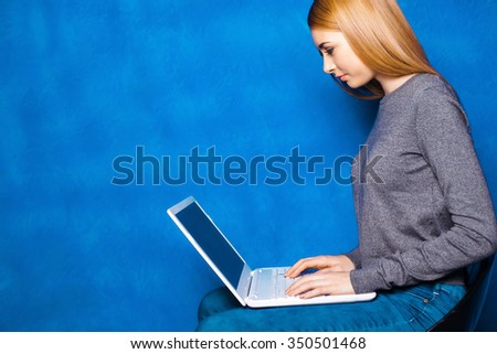 Nice portrait of beautiful girl on blue background. Young woman using laptop - stock photo