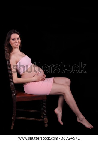 Nice pregnant woman sitting on a chair at studio on a black background
