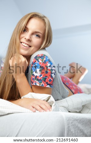 Nice pretty girl smiling in bed in the morning  - stock photo