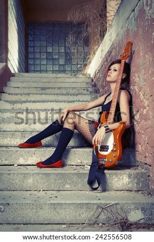 Nice punk/rock player posing on street city location for stylish musician portraits - stock photo