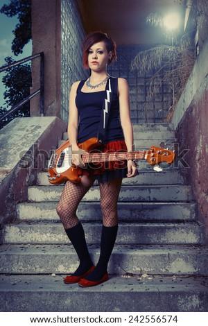 Nice punk/rock short hair bass guitar woman player posing on street city location for stylish musician portraits - stock photo