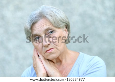nice senior woman on a gray background