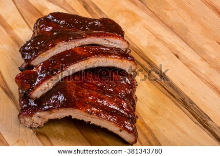 nice serving of bbq ribs on wooden cutting board with copy space