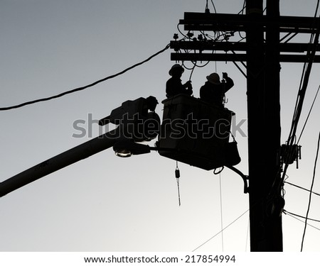 Nice silhouette Image of Men replacing a Power Line - stock photo