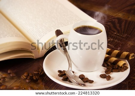 nice small cup of coffee on the white saucer with silver teaspoon with coffee beans and book in the background - stock photo