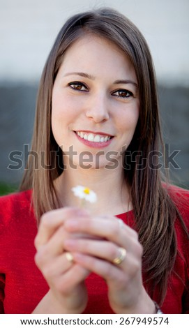 Nice smiling girl holding a beautiful daisy - stock photo