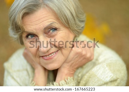 Nice smiling old woman on the yellow leaves background