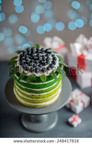 Nice sponge happy birthday cake with mascarpone and grapes with on the cake stand with gift boxes on festive light bokeh background - stock photo