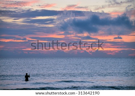 nice sunrise over florida atlantic ocean with fisherman silhouetted in surf - stock photo