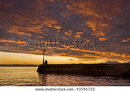 Nice sunrise with fisherman in the bay - stock photo