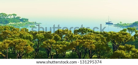 Nice sunset over water and forested  land - stock photo