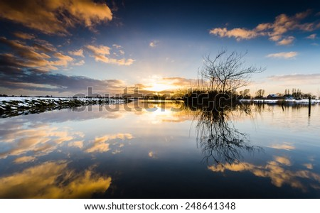 Nice sunset with water reflection and colorfull clouds - stock photo