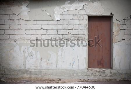 Nice textured wall, big white bricks , plaster fallen off, rusty metal door. - stock photo