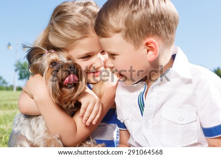 Nice time. Upbeat nice little girl embracing the dog and sitting with boy on blanket while expressing positivity.  - stock photo