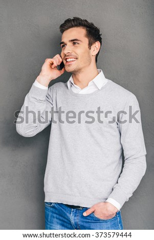Nice to hear your voice! Confident cheerful young man talking on mobile phone and keeping hand in pocket while standing against grey background - stock photo