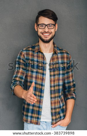 Nice to meet you! Cheerful young man reaching out his hand in greeting you and holding hand in pocket while standing against grey background - stock photo