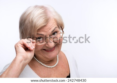 Nice to meet you. Closeup portrait of senior woman adjusting her glasses and smiling while standing against white background - stock photo