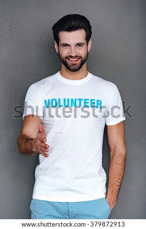 Nice to meet you! Confident young man in volunteer t-shirt reaching out his hand in greeting you and looking at camera with smile while standing against grey background