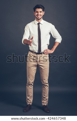 Nice to meet you! Full length of confident young handsome man reaching out his hand in greeting you and looking at camera with smile while standing against grey background - stock photo