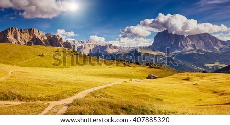 Nice view of the alpine valley and blue sky. Dramatic scene. Location famous resort Gardena, Sassolungo (Langkofel) and Sella group, National Park Dolomites, South Tyrol. Italy, Europe. Beauty world. - stock photo