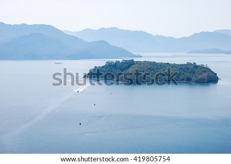 Nice view on little island and boat in Aegean Sea - stock photo