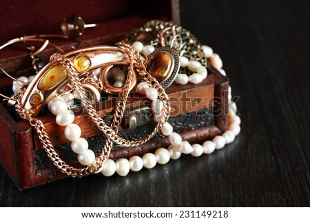 Nice vintage open box full of various jewelry on dark wooden background - stock photo