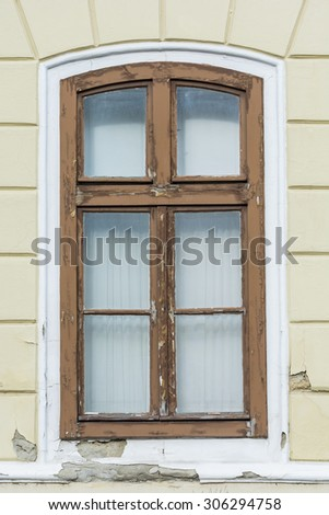 Nice vintage window on a yellow wall. - stock photo