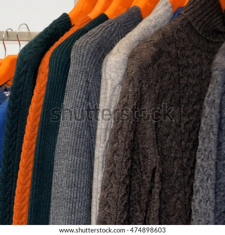 Nice warm colorful sweaters hang on hangers inside of a shopping mall. Beautiful clothes for winter autumn season. Fashion industry for men. Wool things for fall. Classic design. Merchandise in shop