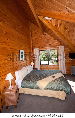 Nice warm interior of mountain wooden lodge double bedroom. Fox Glacier Lodge, Fox Glacier, West Coast, South Island, New Zealand. - stock photo