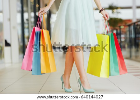Nice woman's legs wearing light dress and hills, holding colorful shopping bags in two hands, standing in shopping mall, shopping concept, portrait.