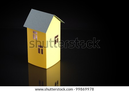 Nice yellow paper house with green roof on dark background with free space for text