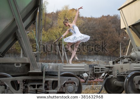 Nice young ballerina making a pose while standing on a freight wagon. She is wearing a white tutu with ballet shoes. There are many trees behind her. Outdoor. Horizontal. - stock photo