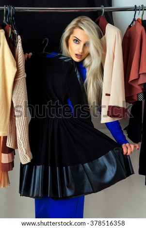 Nice young blonde woman choosing a dress in clothing store. Beautiful young lady with a lot of clothes. Shopping concept. - stock photo