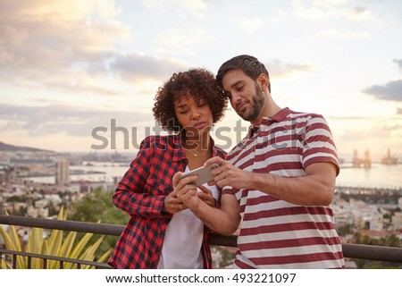 Nice young couple looking at a cellphone while standing on a bridge that overlooks the city behind them, wearing casual clothing