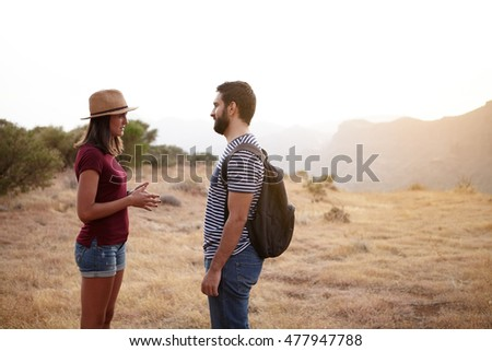 Nice young couple talking on a plato on a mountain in bright sunshine wearing t-shirts and jeans and a straw hat and backpack