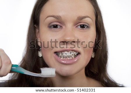 nice young dark hair girl holding toothbrush and wearing bracket system isolated over white - stock photo
