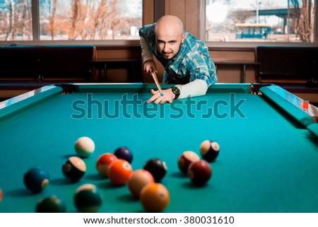 Nice young guy plays pool billiards. Billiard sport concept. American pool billiard. Pool billiard game. - stock photo