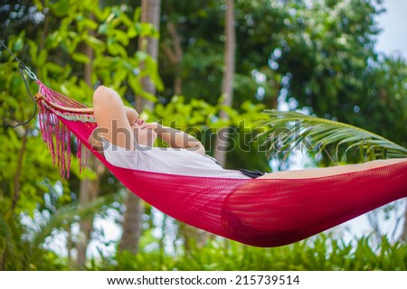Nice young lady listen music in hummock under palm trees on tropical beach. Wake up touch eyes