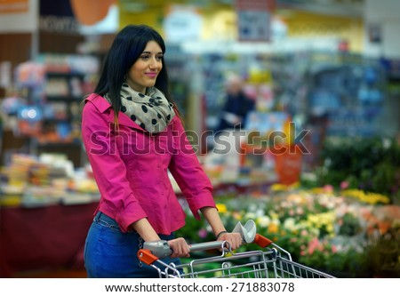 Nice Young Lady with Shopping Cart at the Supermarket - stock photo