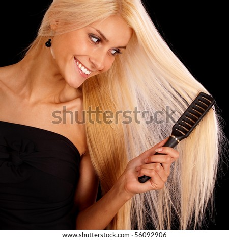 Nice young woman combs hair and smiles, it is isolated on black background.