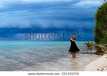 Nice young woman dancing on the beach with a tropical storm - stock photo