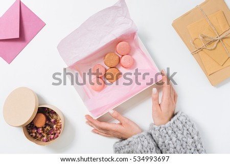 Nice young woman holding a box with macaroons