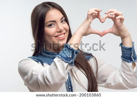 Nice young woman make heart shape by her fingers on the head level isolated on grey background - stock photo