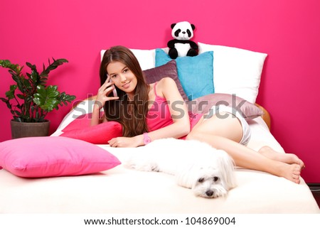 nice young woman speaking on cellphone with her girlfriend and lying with her white dog - stock photo